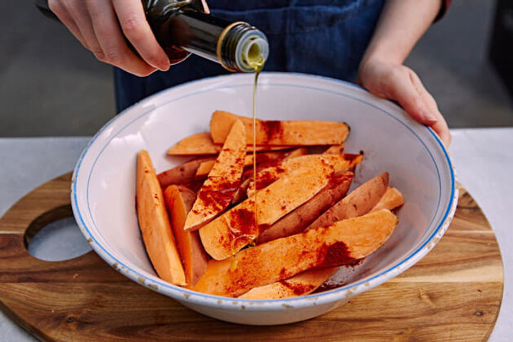 Image of raw sweet potato wedges being dressed with olive oil being poured over them