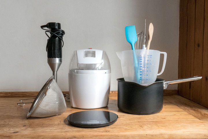 Image of equipment needed to make gelato including a sieve, blender, ice cream machine, pan and measuring jug