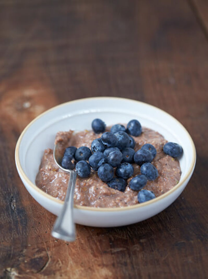 bowl of porridge mixed with granola dust topped with blueberries