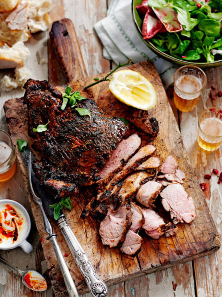 Image of cooked, butterflied leg of lamb on a wooden chopping board