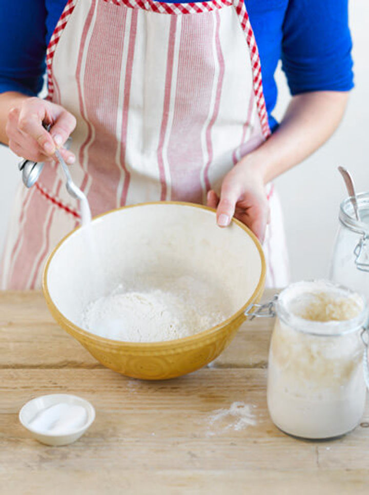Image of flour and salt being mixed in a bowl to make sponge for sourdough