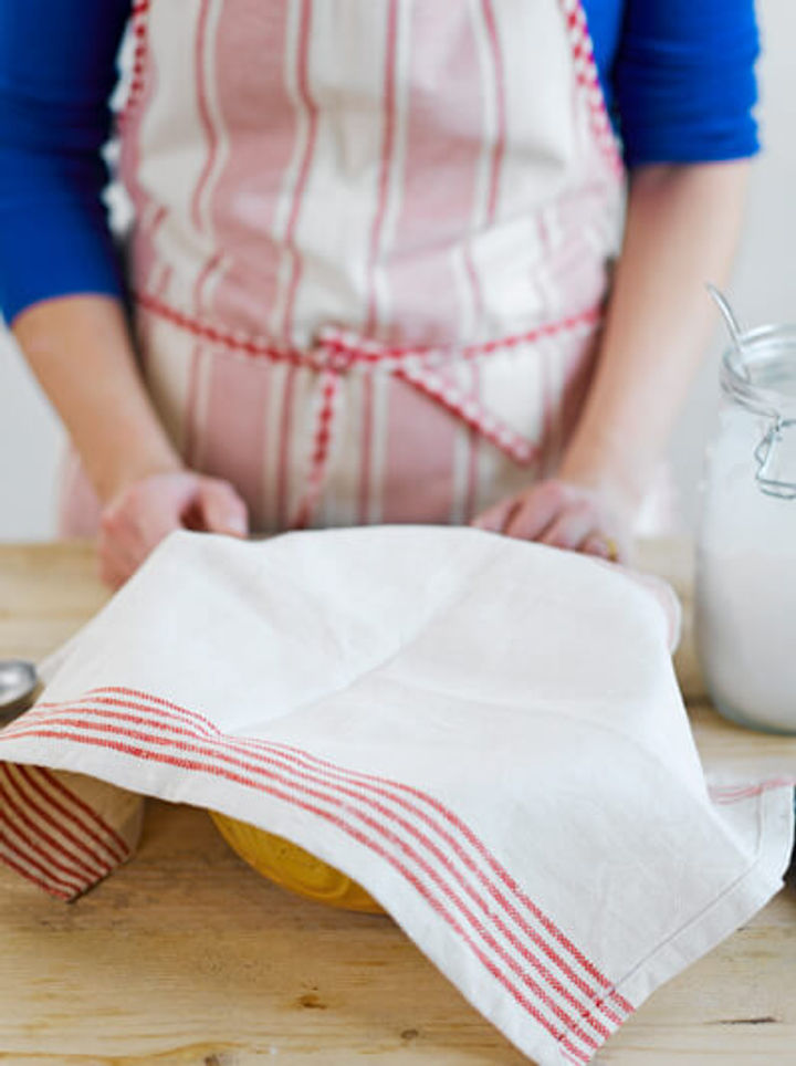 Image of sourdough mixture covered with a tea towel to rise