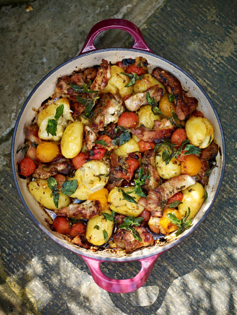 Crispy & sticky chicken thighs with squashed new potatoes & tomatoes
