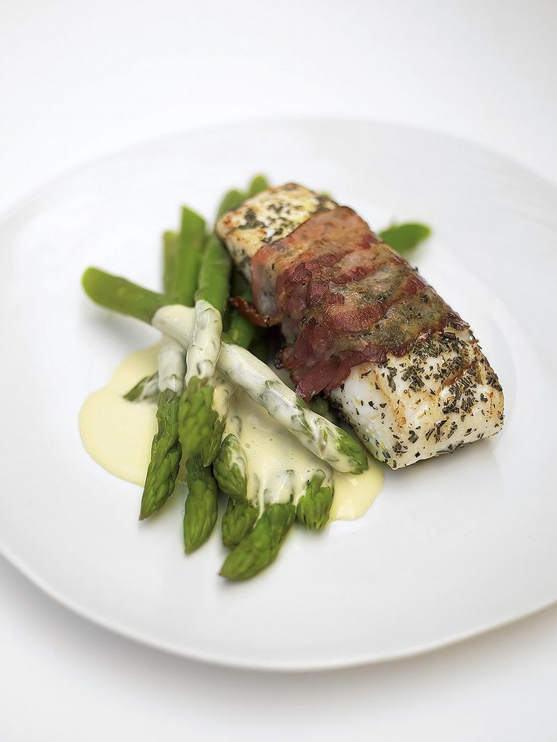 Delicious roasted white fish wrapped in smoked bacon with lemon mayonnaise and asparagus