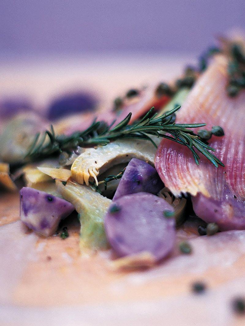Rochenflügel mit artischocken, violetten kartoffeln und kapern in der papierhülle gegart